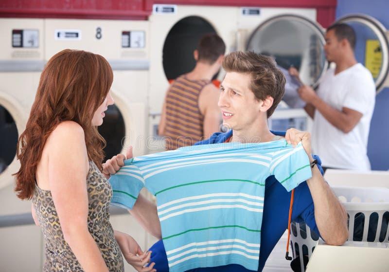 Mann, der geschrumpftes T-Shirt ausdehnt stockfoto