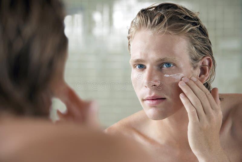 Mann, der Gesichtscreme aufträgt stockfotos