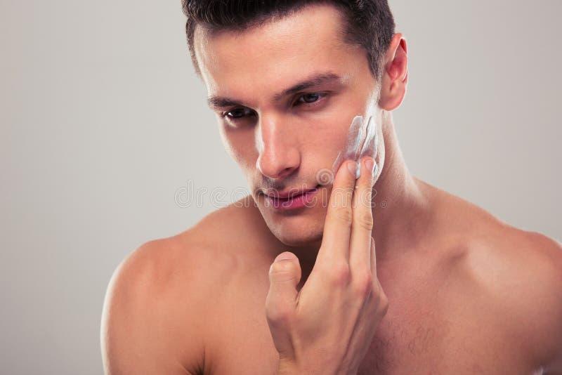 Mann, der Gesichtssahne aufträgt stockbild
