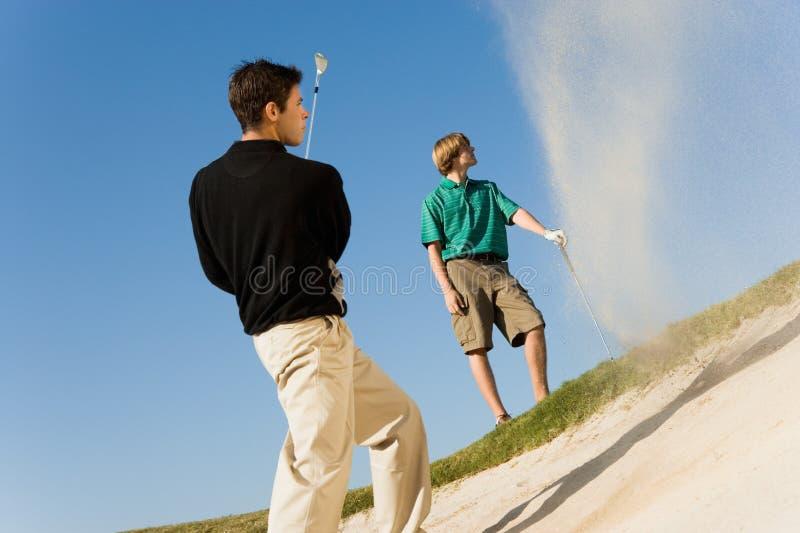 Mann, der Golfball aus einem Sandfang heraus schlägt lizenzfreie stockbilder