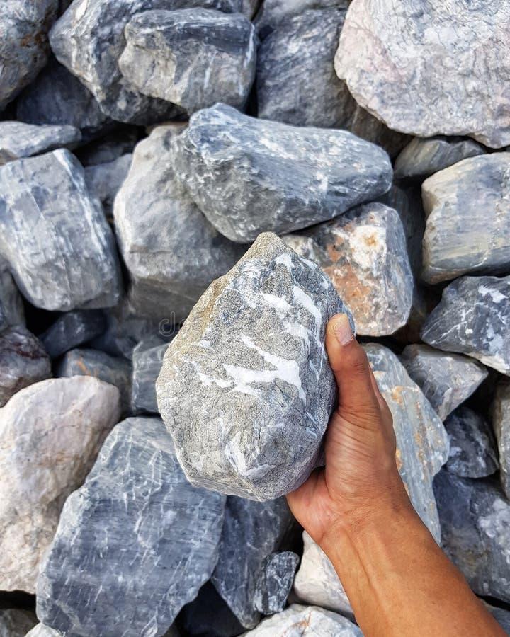 Mann, der Granitfelsen hält stockfotos