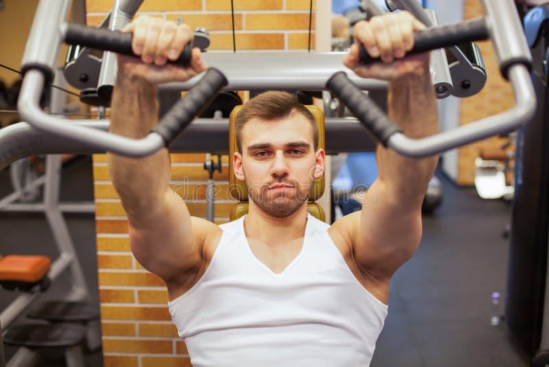 Mann, der an der Gymnastik trainiert Der Eignungsathlet, der Kasten tut, trainiert auf vertikaler Bankdrückenmaschine lizenzfreie stockbilder
