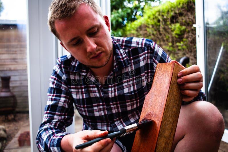 Mann, der hölzernes Brett lackiert Heimwerkenkonzeptbild Junge, der hölzernes Brett mit Malerpinsel malt Bürste in der Hand und c lizenzfreie stockfotos