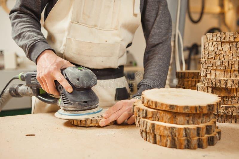 Mann, der hölzernes rundes Werkstück hält und mit Schleifmaschine verarbeitet stockfotografie