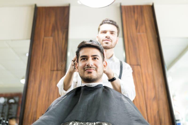 Mann, der Haar getrimmt vom Herrenfriseur in Barber Shop erhält stockfotografie
