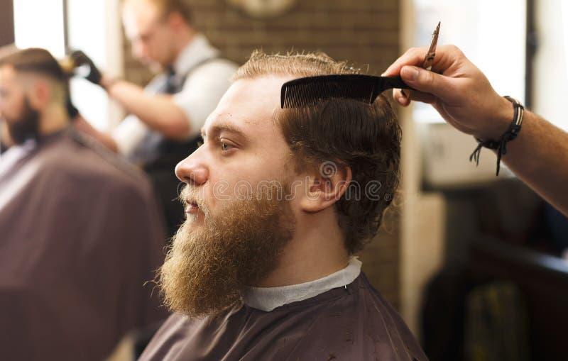 Mann, der Haarschnitt durch Herrenfriseur am Friseursalon erhält lizenzfreies stockbild