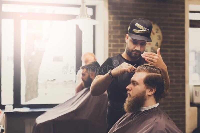 Mann, der Haarschnitt durch Herrenfriseur am Friseursalon erhält lizenzfreie stockfotos