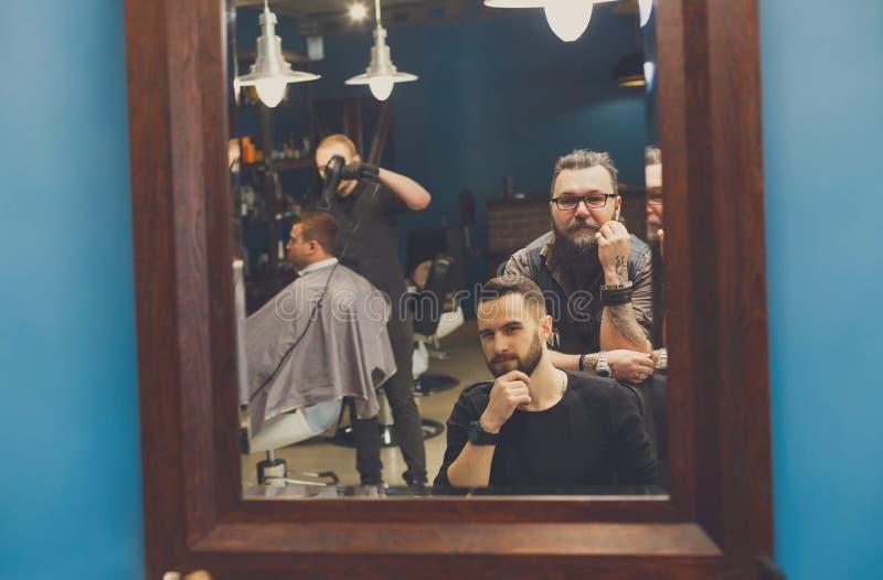 Mann, der Haarschnitt durch Herrenfriseur am Friseursalon erhält stockbilder
