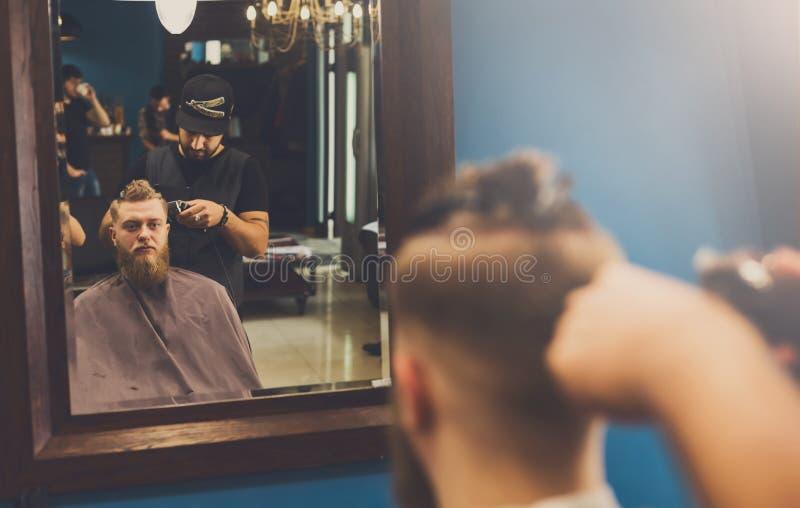 Mann, der Haarschnitt durch Herrenfriseur am Friseursalon erhält stockfotos