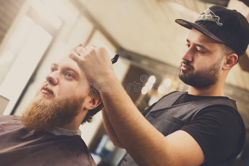 Mann, der Haarschnitt durch Herrenfriseur am Friseursalon erhält lizenzfreies stockfoto
