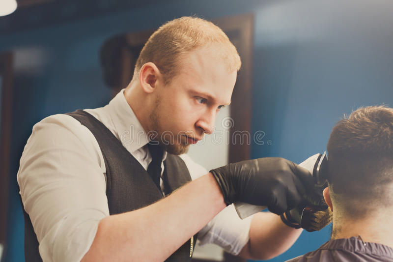 Mann, der Haarschnitt durch Herrenfriseur am Friseursalon erhält lizenzfreie stockfotografie
