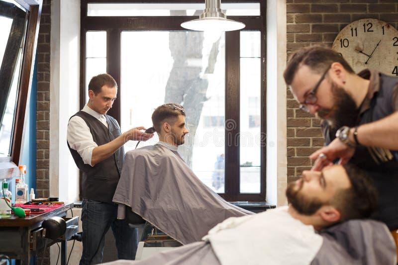 Mann, der Haarschnitt durch Herrenfriseur am Friseursalon erhält lizenzfreie stockbilder