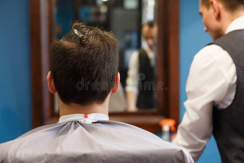 Mann, der Haarschnitt durch Herrenfriseur am Friseursalon erhält stockbild
