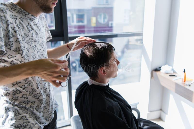 Mann, der Haarschnitt am Friseursalon erhält Friseur, der Haar des Kunden am Salon anredet lizenzfreie stockfotos