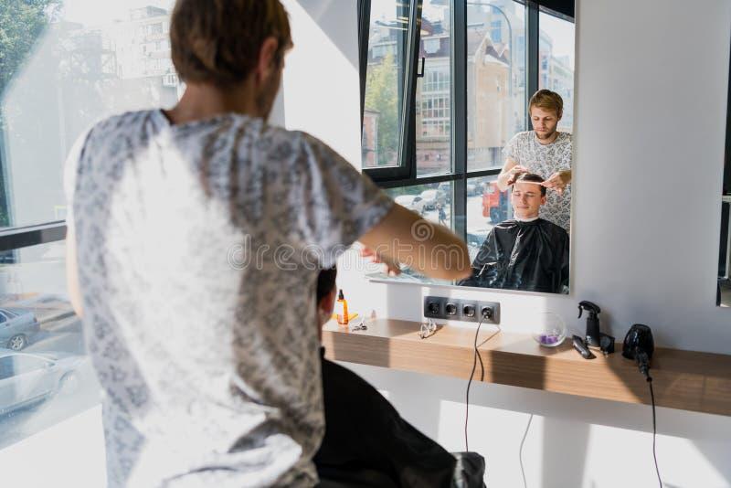 Mann, der Haarschnitt am Friseursalon erhält Friseur, der Haar des Kunden am Salon anredet stockfoto
