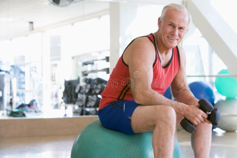 Mann, der Handgewichte auf Schweizer Kugel an der Gymnastik verwendet lizenzfreies stockfoto