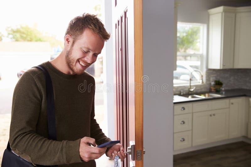 Mann, der Handy überprüft, wie er Tür der Wohnung öffnet stockfotografie