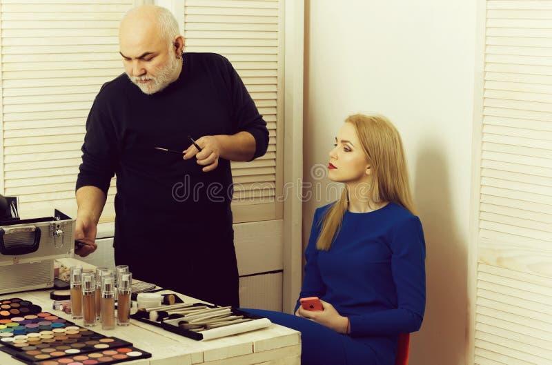 Mann, der Handy mit Make-upbürsten überprüft lizenzfreies stockfoto