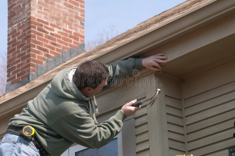 Mann, der an Haus arbeitet stockbilder