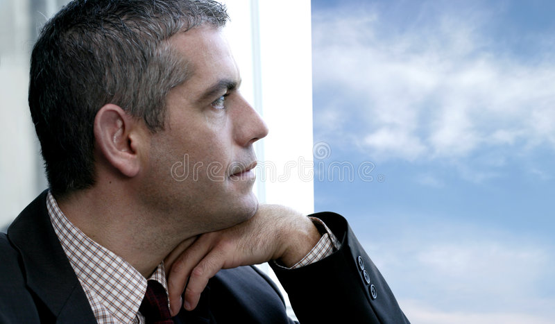 Mann, der heraus das Fenster schaut lizenzfreies stockfoto