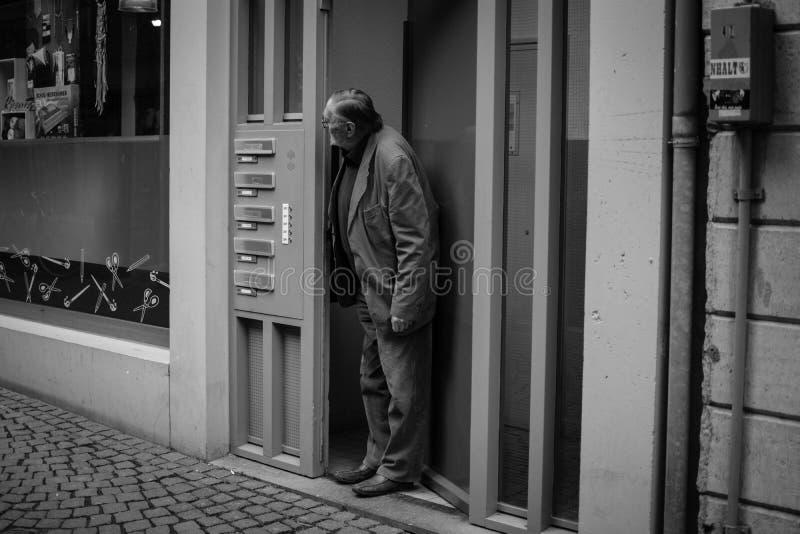 Mann, der heraus die Tür schaut lizenzfreie stockfotografie