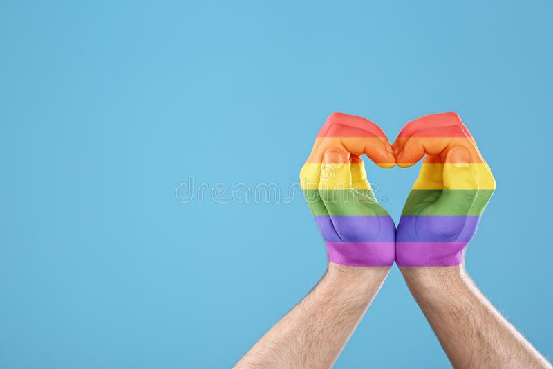 Mann, der Herz mit den Händen gemalt in LGBT-Flagge auf Farbhintergrund macht Homosexuelle Gemeinschaft stockbild