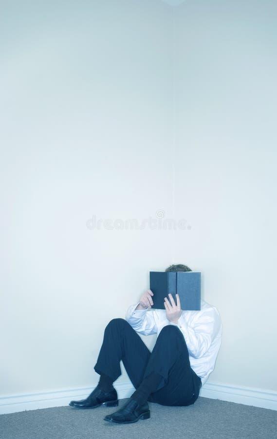 Mann, der hinter einem Buch sich versteckt lizenzfreies stockfoto