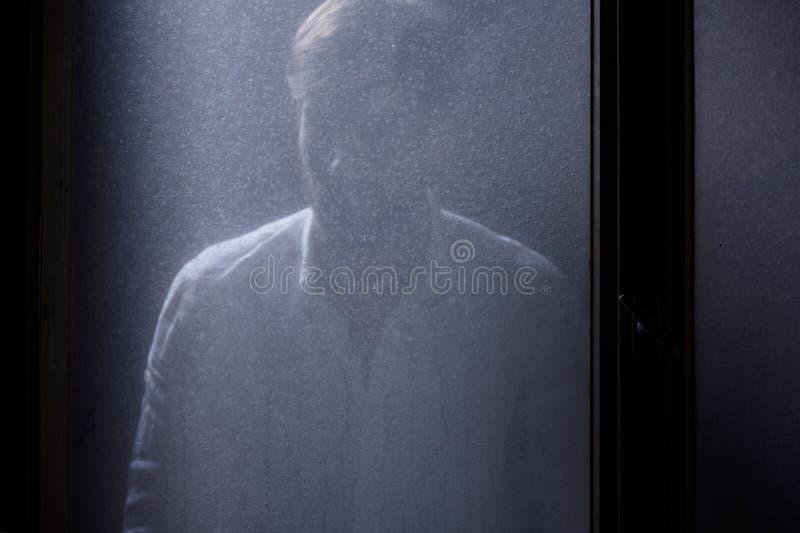 Mann, der hinter Fenster steht lizenzfreie stockbilder