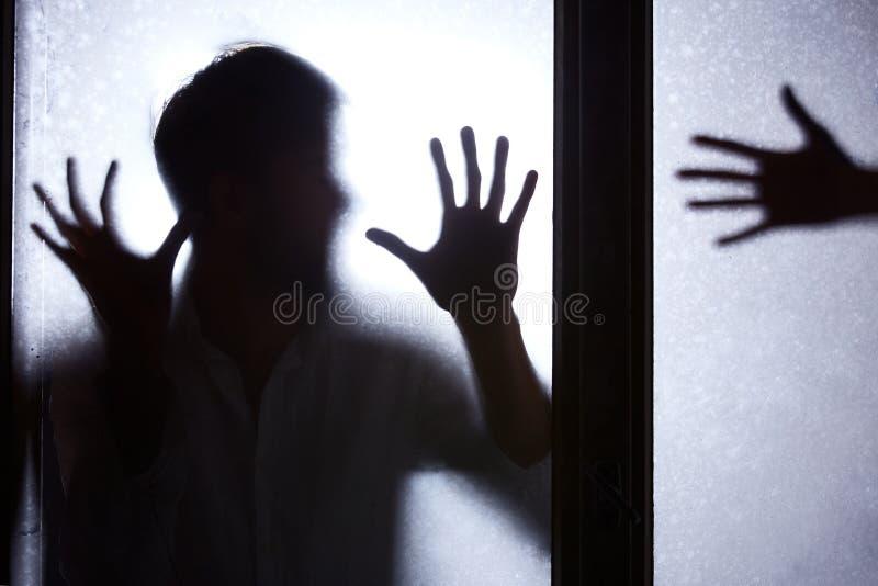 Mann, der hinter Glastür steht stockfotografie