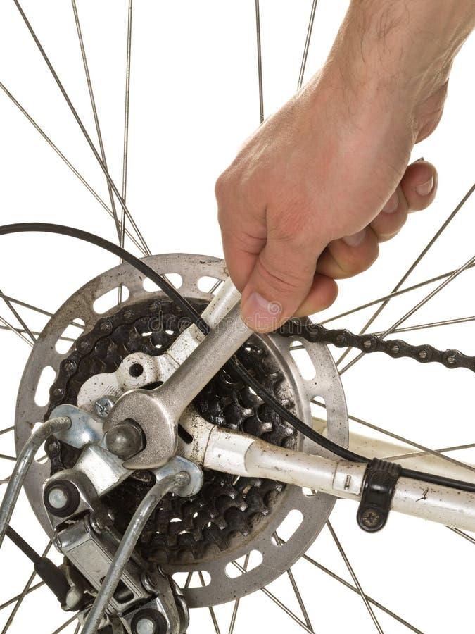Mann, der Hinterrad auf einem Fahrrad repariert lizenzfreie stockbilder
