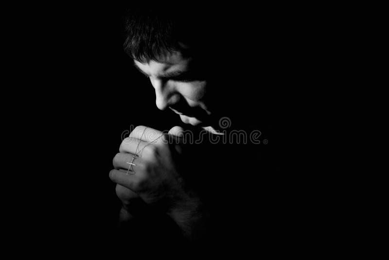 Mann, der hinunter das Beten zum Gott knit stockbilder