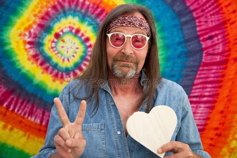 Mann der Hippie von mittlerem Alter, der das Siegeszeichen macht lizenzfreies stockfoto