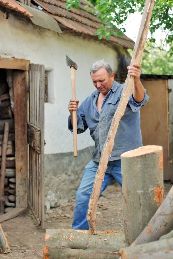 Mann, der Holz hackt stockfotos