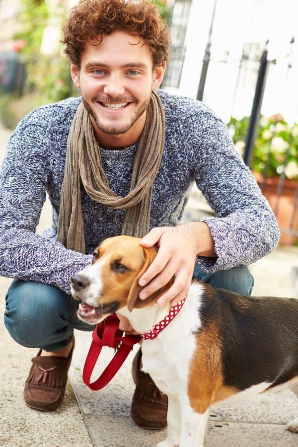Mann, der Hund für Weg auf Stadt-Straße nimmt lizenzfreie stockfotos