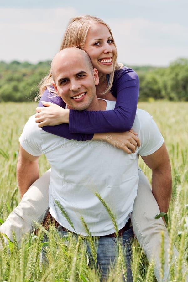 Mann, der ihre Freundin huckepack trägt stockfotografie