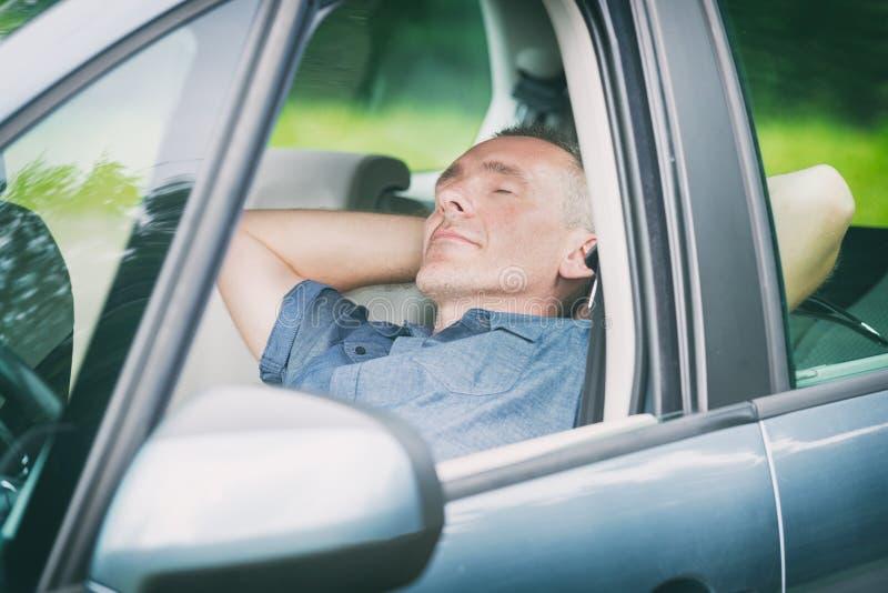 Mann, der im Auto schläft stockbild