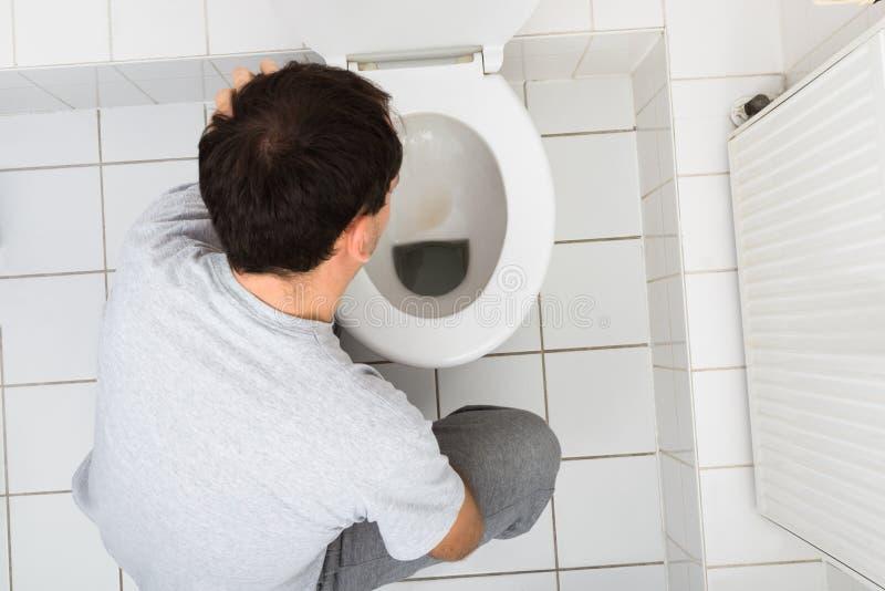 Mann, der im Badezimmer sich erbricht stockbild