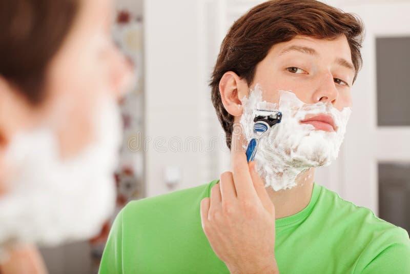 Mann, der im Badezimmer sich rasiert lizenzfreie stockbilder