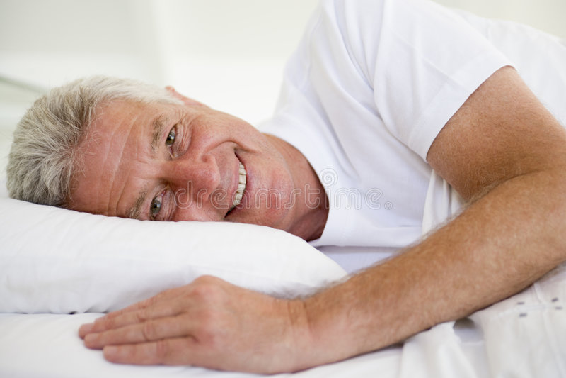 Mann, der im Bett liegt lizenzfreie stockbilder
