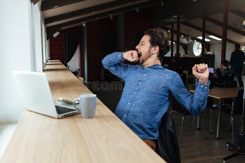 Mann, der im Café gähnt stockfoto