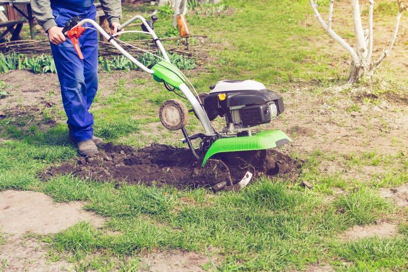 Mann, der im Frühjahr Garten mit Pflügermaschine bearbeitet lizenzfreie stockbilder