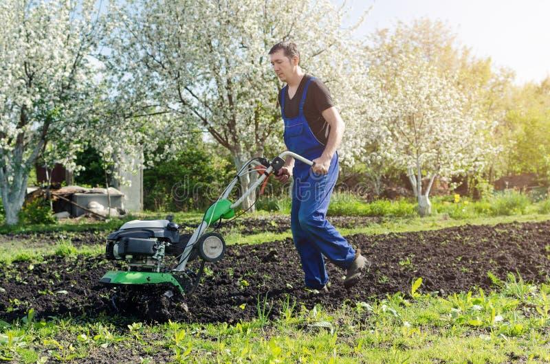 Mann, der im Frühjahr Garten mit Pflügermaschine bearbeitet stockfoto