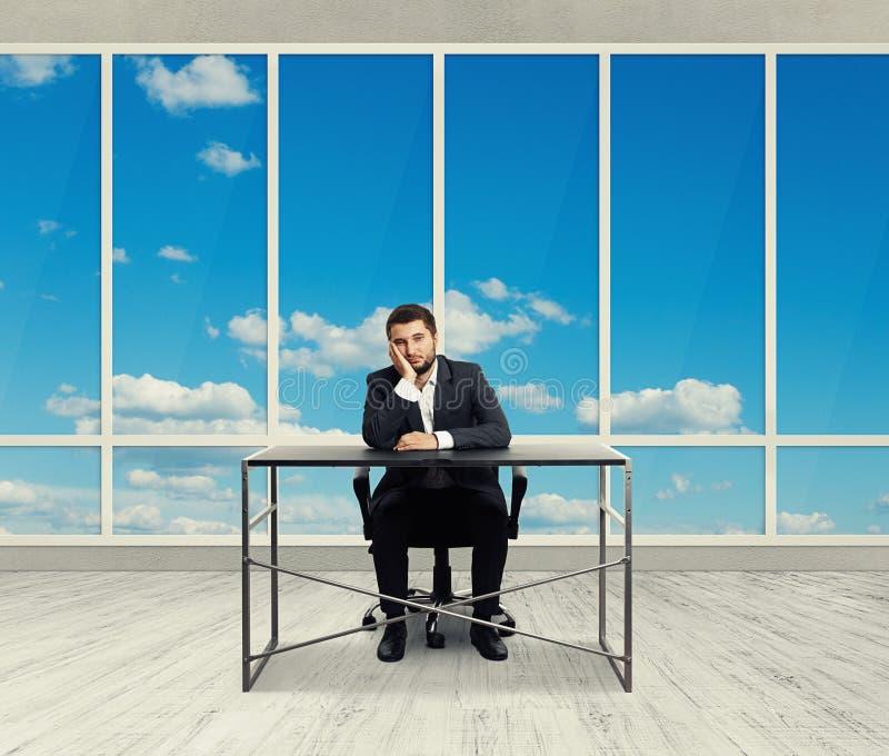 Mann, der im leeren Büro sitzt lizenzfreie stockfotos