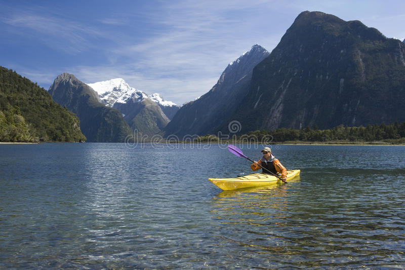 Mann, der im Mountainsee Kayak fährt stockbilder