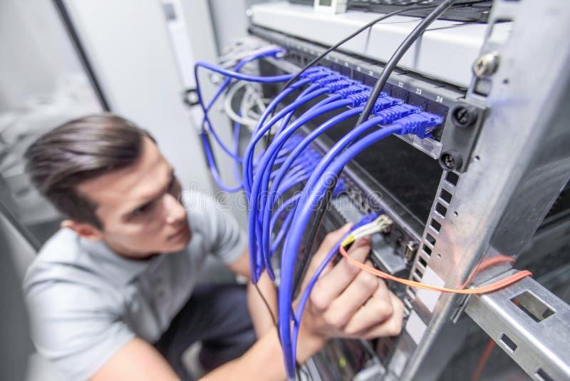 Mann, der im Netzwerk-Server-Raum arbeitet lizenzfreies stockbild