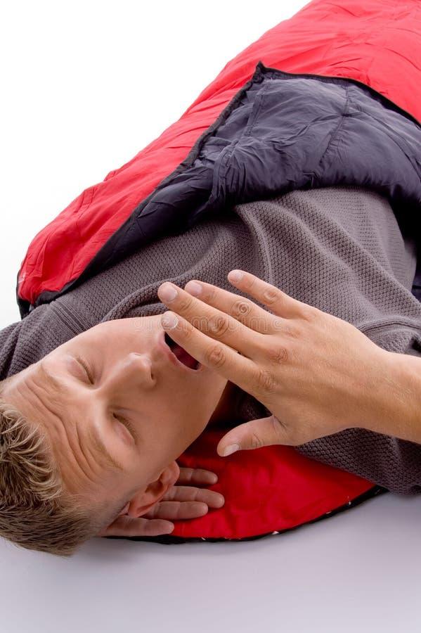 Mann, der im Schlafsack gähnt stockbilder