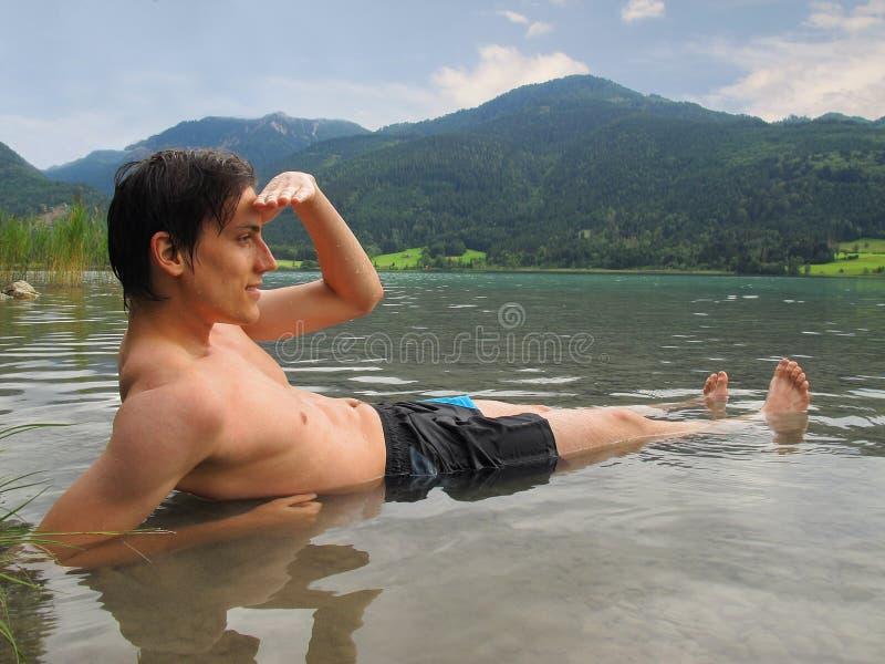 Mann, der im See liegt stockbild