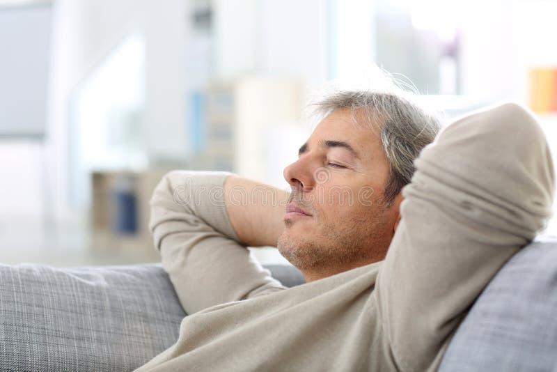 Mann, der im Sofa ein Schläfchen hält lizenzfreie stockfotos