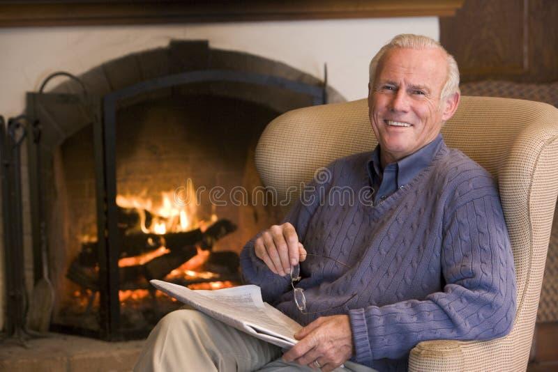 Mann, der im Wohnzimmer durch Kamin sitzt stockfoto
