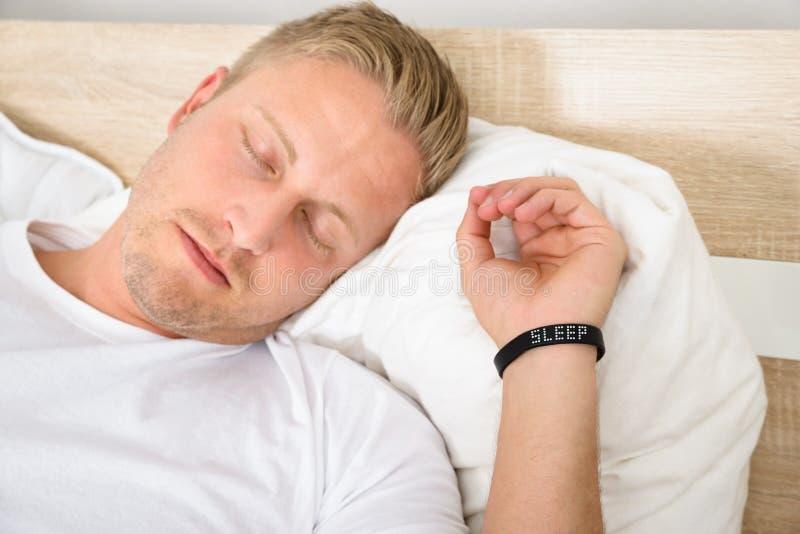 Mann, der intelligente Manschette beim Schlafen trägt stockbild
